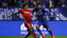 Tianjin Quanjian midfielder Axel Witsel (L) competes for the ball against Shanghai Shenhua's Carlos Tevez