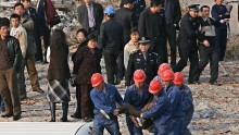 Corrupt officials being escorted to a van by construction workers.